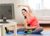 Smiling teenage girl streching on floor at home — Stockfoto