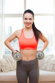 Smiling girl exercising with dumbbells — Stockfoto