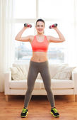 Smiling teenage girl exercising with dumbbells — Stock Photo