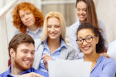 Team with papers and take away coffee on staircase — Stock Photo