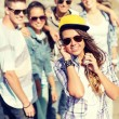Teenage girl with headphones and friends outside — Stock Photo #44626877