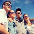 Smiling teenagers in sunglasses hanging outside — Stock Photo