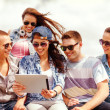 Group of smiling teenagers looking at tablet pc — Stockfoto