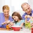 Happy family with two kids making dinner at home — Stock Photo #44628399