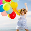 Happy jumping girl with colorful balloons — Stock Photo #44628419