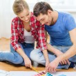 Smiling couple looking at color samples at home — Stock Photo #44629361