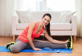 Smiling teenage girl streching on floor at home — Stock Photo