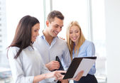Business team looking at clipboard — Stock Photo