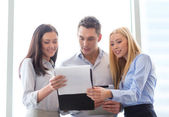 Business team looking at clipboard — Stockfoto