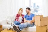улыбаясь, пара, отдыхая на диване в новом доме — Стоковое фото