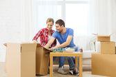 Smiling couple unpacking kitchenware — Stock Photo
