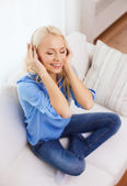 Smiling young girl in headphones at home — Stockfoto