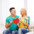 Smiling couple with red heart on sofa in new home — Stock Photo #44708461