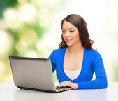 Smiling woman in blue clothes with laptop computer — Stock Photo