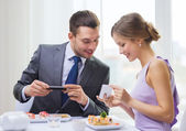 Smiling couple with sushi and smartphones — Stock Photo