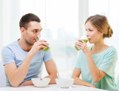Smiling couple having breakfast at home — Stok fotoğraf