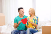 Smiling couple with red heart on sofa in new home — Stock Photo