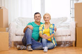 Smiling couple sitting on the floor in new house — Stockfoto