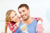 Smiling couple covered with paint with paint brush — Stock Photo