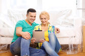Smiling couple with tablet pc in new home — Stock Photo