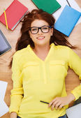 Smiling female student in eyeglasses with pencil — Stok fotoğraf