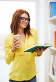 Female student in eyeglasses with book and coffee — Stock Photo
