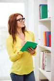 Female student in eyeglasses with textbook — Stock Photo