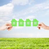 Man and woman hands with many green paper houses — Stock Photo