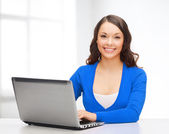 Smiling woman in blue clothes with laptop computer — Stockfoto