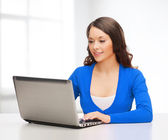 Smiling woman in blue clothes with laptop computer — 图库照片