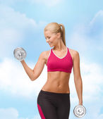 Smiling woman lifting steel dumbbell — Foto Stock
