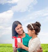 Hediye kutusu ile mutlu anne ve çocuk kız — Stok fotoğraf