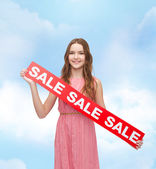 Young woman in dress with sale sign — Stockfoto