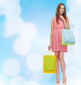 Smiling woman in dress with many shopping bags — 图库照片