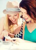 девочки, глядя на смартфон в кафе — Стоковое фото