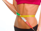 Close up of trained belly with measuring tape — Stock Photo