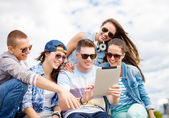 Group of smiling teenagers looking at tablet pc — Stock fotografie