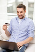 Smiling man working with laptop and credit card — Stockfoto