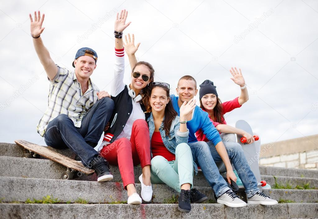 group of smiling teenagers hanging out stock photo syda