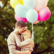 Couple with colorful balloons kissing in the park — Stock Photo #45042391