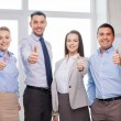 Business team showing thumbs up in office — Stock Photo