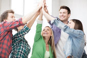 Happy students giving high five at school — Stock Photo