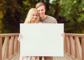 Couple on the bridge with blank white board — Stockfoto