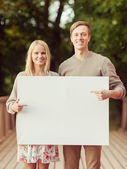 Couple on the bridge with blank white board — Foto Stock