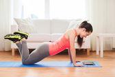 Smiling teenage girl doing push-ups at home — Stock Photo