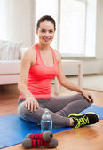 Smiling girl with bottle of water after exercising — Stockfoto