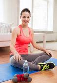 улыбающаяся девушка с бутылкой воды после тренировки — Стоковое фото