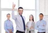 Empresário no escritório com equipe na volta a sorrir — Fotografia Stock