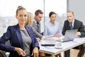 Geschäftsfrau mit Gläsern mit Team auf der Rückseite — Stockfoto