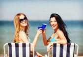 Meninas com bebidas em cadeiras de praia — Foto Stock